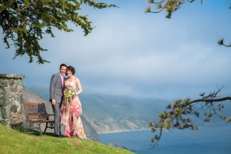 Wedding couple standing on grassy hill overlooking blue ocean